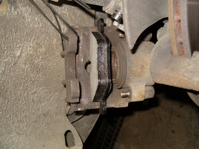 And then place the inner brake pad (with the metal springs into the hole of the caliper piston) into the brake caliper.