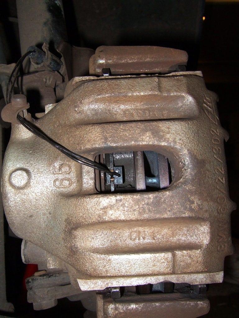 Correctly located brake pad wear sensor wire.