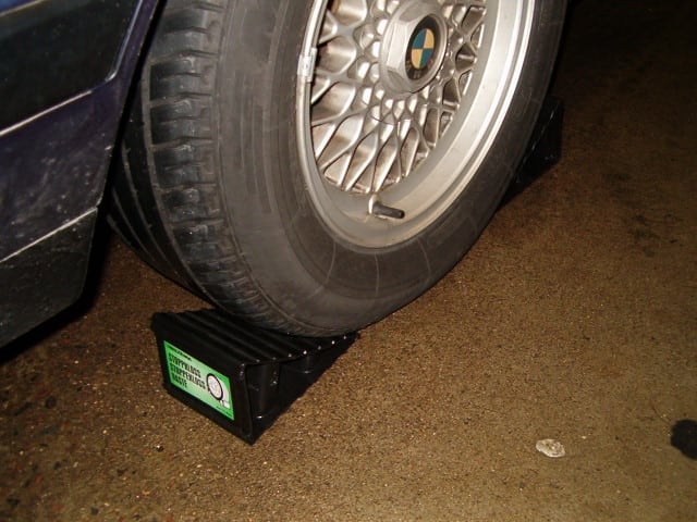 A wheel chocked using two plastic chocks placed on each side.