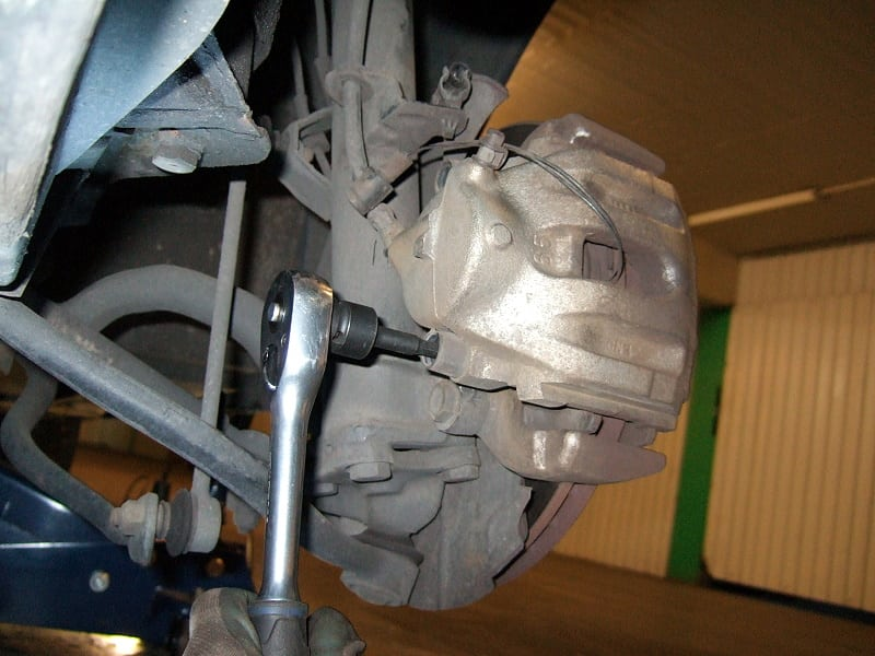 Removing the brake caliper guide bolts with a proper socket and ratchet wrench.