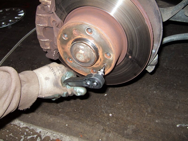 Removing the small (and usually stubborn) bolt holding the brake disc.