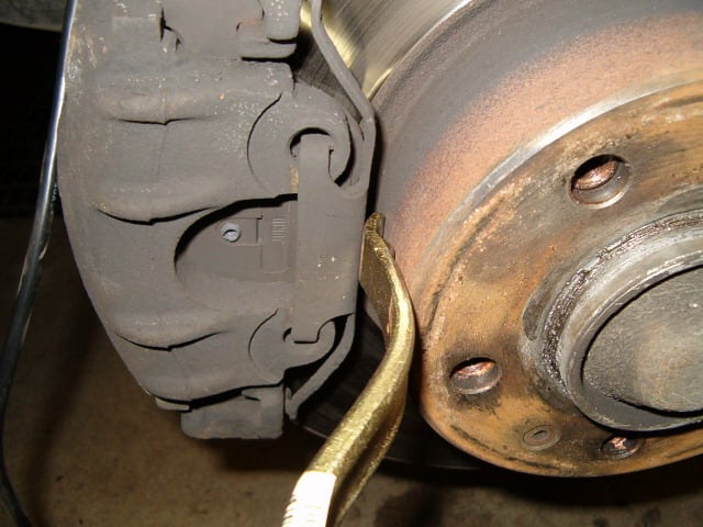 Place the tire lever between the anti-rattle clip and the wheel hub and push the clip away from the wheel hub.